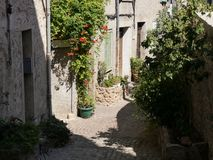 Narrow alley in semi-shade, southern France,Pot and tub plants, typical sandstone for houses, coarse cobblestones, pipes for. Installations on the walls royalty free stock photo