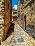 Narrow alley with stone floor. Narrow alley with soil and stone houses stock photos