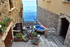 Narrow alley to the sea in Scilla. Narrow alley to the sea in the od fisherman village of Scilla in Calabria, southern Italy royalty free stock image