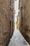 Narrow alleys between vertiginous walls of ancient buildings. Narrow alleys between the vertiginous walls of ancient buildings in the historic center of Rimini Stock Photo