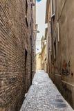 Narrow alleys between vertiginous walls of ancient buildings Stock Photo
