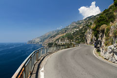 Narrow Amalfi Coast Mountain Road. Stunning view over the picturesque Amalfi coast in Italy - crystal clear Meditteranean sea, rocky mountains, blue sky and a Stock Images