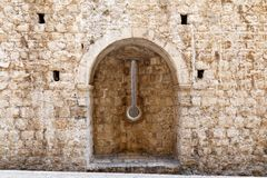 Narrow Arrowslit in Dubrovnik Stone Walls, Croatia. A narrow arrowslit, firing slit or embrasure in original thick stone fortification walls, Dubrovnik Old Town royalty free stock photo