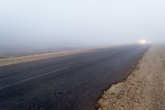 Narrow asphalt road in the fog Royalty Free Stock Photo