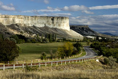 The narrow asphalt road in the picturesque bloomin. G steppe to the distant mountains 2 Stock Photo