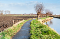 Narrow bike path besides a meandering river. Stock Image
