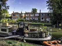 Narrow boat barge under the green trees in Cambridge Stock Images