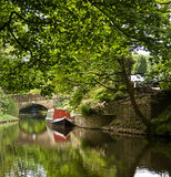 Narrow boat on the canal. Narrow boat moored on the canal near a bridge Royalty Free Stock Images