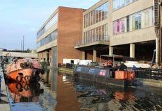 Narrow boat on canal at Paddington, London. Narrow boat moving along canal at Paddington Basin by Paddington station in London heading towards Little Venice with Royalty Free Stock Photo
