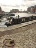 A nArrow boat moored in historic docks. Historic docks with moored boats Royalty Free Stock Image
