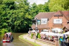 Narrow boat passes classic English pub Stock Photos