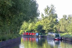 Narrow boats on the Trent and Mersey canal in Cheshire UK. Traditional narrow boats moored on the Trent and Mersey canal in Cheshire England UK royalty free stock photos