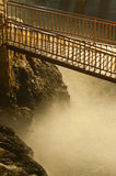 Narrow bridge over the wild river and rocks. Narrow wooden steel bridge over the wild river and rocks at night Stock Photos