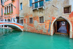 Narrow canal along old brick houses. Venice, Italy. Royalty Free Stock Images