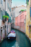 Narrow canal with a boat in Venice Stock Photo