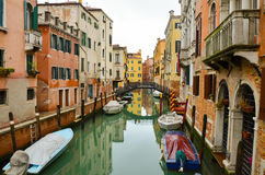 Narrow canal with boats and the reflection of the old colourful houses in the water, Venice, Italy Stock Images