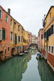 Narrow canal with boats and the reflection of the old colourful houses in the water, Venice, Italy Royalty Free Stock Photography