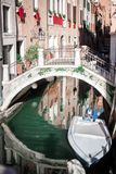 A narrow canal with green water in the lane of Venice, Italy, a small bridge, a motor boat.  royalty free stock photos