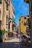 Narrow canal among old colorful brick houses in Venice Stock Photos