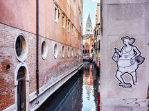 Narrow canal among old houses in Venice. VENICE, ITALY - JULY 2,2014: City landscape. Old brick houses in Venice and typical narrow Venetian canals with bridges royalty free stock photos