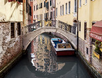 Narrow canal among old houses in Venice. VENICE, ITALY - JULY 2,2014: City landscape. Old brick houses in Venice and typical narrow Venetian canals with bridges royalty free stock images
