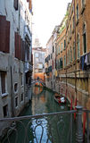 Narrow canal in Venice. Scenic view of buildings on narrow canal with arched bridge in background, Venice, Veneto, Italy Stock Image