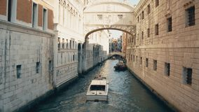 Motorboat moving along narrow canal in Venice between old buildings, Italy. Narrow canal in Venice between old buildings stock images