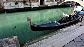 In the narrow canal of Venice there is a gondola waiting for the next couple in love royalty free stock photography