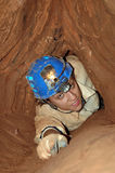 Narrow cave passage with caver. In a extreme situation stock images