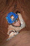 Narrow cave passage with a caver. Narrow cave passage with a cave explorer royalty free stock photo