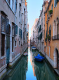 Narrow channel in venice with some boats at dawn Stock Image