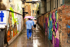 Narrow channels of graffiti and people Royalty Free Stock Image