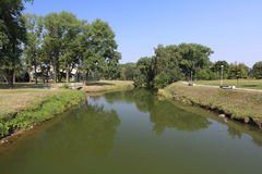 Narrow city river. Narrow small river in the city park with stagnant water Stock Photo