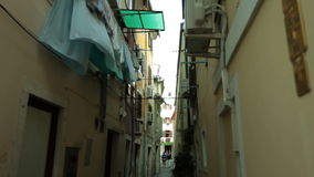 Narrow city street with pegged out clothes between the buildings. Narrow coastal city street occupied with pegged clothes stock footage