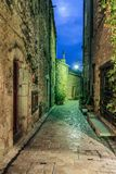 Narrow cobbled street with flowers in the old village at night, stock image