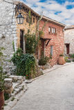 Narrow cobbled street with flowers in the old village Tourrettes Royalty Free Stock Photos