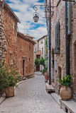 Narrow cobbled street with flowers in the old village Tourrettes-sur-Loup , France. royalty free stock photography