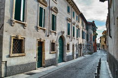Narrow cobbled street in old Italian city Stock Photos