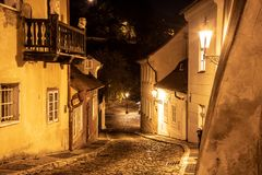 Narrow cobbled street in old medieval town with illuminated houses by vintage street lamps, Novy svet, Prague, Czech. Republic. Night shot stock images