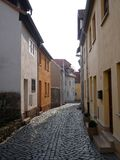 Narrow cobbled urban street with houses Stock Photo