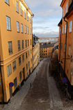 Narrow cobblestone alley and old houses in central Stockholm Stock Images