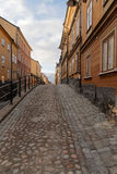 Narrow cobblestone alley and old houses in central Stockholm Stock Photos