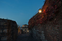Narrow cobblestone path with an old fashioned lantern inside Kalemegdan fortress at blue hour, Belgrade Stock Photos