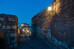 Narrow cobblestone path with an old fashioned lanterns inside Kalemegdan fortress at blue hour, Belgrade Royalty Free Stock Images