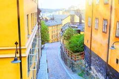The narrow cobblestone street Bastugatan in Sodermalm with medieval houses in Stockholm at summer sunny day. The narrow cobblestone street Bastugatan in stock photo