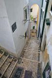 Narrow and colorful street in Alfama neighborhood with cobbled stairs in Lisbon, Portugal Royalty Free Stock Photos