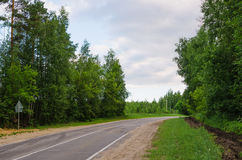 Narrow country road near a forest Royalty Free Stock Image