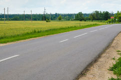 Narrow country road near a meadow Royalty Free Stock Photography