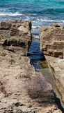 Narrow crack in the rocks at sea coast Stock Photos