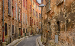 Narrow decrepit red brick street in Toulouse Stock Images